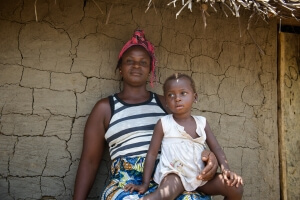 Rebecca Mulvah, 34, and her daughter Blessing, 2, in Balakatala, Liberia. Rebecca and her daughter became sick with Ebola in November 2014 after Rebecca's mother became sick. Her mother cared for the first person sick with Ebola in the village. Rebecca's son also became sick, and died. She went to live in the bush for a time because there were rumors that neighboring villagers wanted to burn her village because of the Ebola fears. To help prevent the spread of Ebola in the future, Caritas staff came to Balakatala, Liberia, to promote better hygiene and distribute hygiene kits (50 buckets, 5 bars of soap per bucket, and 1 bottle of bleach per bucket).