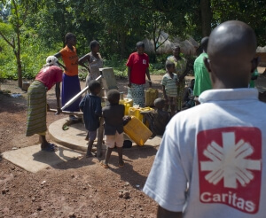 Families fetching clean water for their use from a borehole installed by Caritas in Yambio, South Sudan. The clean water aids in preventing spread of diseases such as cholera and typhoid.