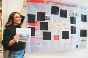 Steffi Vermeire, verantwoordelijke burgerschapseducatie, en de banner die gebruikt wordt tijdens workshops